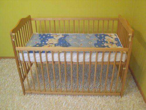 Łóżeczko dla dziecka z drewna bukowego z opuszczanym bokiem.