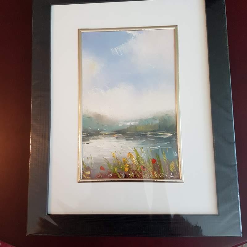 Kupić Sielankowy pejzaż przedstawiający jezioro i usytuowany w tle las, na brzegu znajdziemy czerwone maki i żółte kwiaty, obraz pogodny i słoneczny utrzymany w tonacji błękitów.