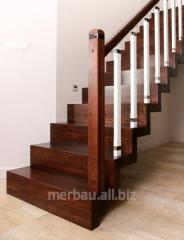 Schody dywanowe, schody mieszkaniowe pod dywan z drewnianą poręczą której słupki wykończone są metalową obręczą.