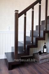 Schody dywanowe, schody drewniane pod dywan ze słupami poręczy wykończonymi metalową opaską.