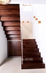 Drewniane schody podestowe z metalową poręczą ze