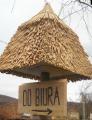 Tablica informacyjna wykonana z drewna połączona z daszkiem z trzciny.