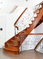 Schody gięte, konstrukcja pełna z metalową balustradą pełniącą funkcję ozdobną (metaloplastyka) i drewnianą poręczą.