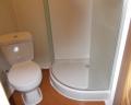 Dwuosiowa przyczepa socjalna i sypialniana wyposażona w łazienkę z prysznicem i aneks kuchenny.