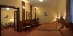 Apartament 4- osobowy, gdzie w sypialni znajduje się łóżko małżeńskie oraz 2 łóżka pojedyncze, a w pokoju dziennym komplet wypoczynkowy